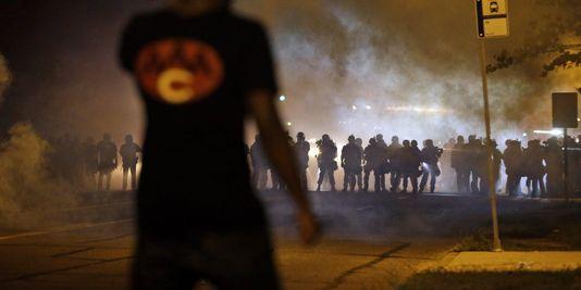 Ein demonstrant vor polizei Ferguson in einem vorort von St. Louis (Missouri) bei der vierten nacht der gewalt, die schütteln die stadt seit dem tod von Michael Brown, der am 9. august 2014.